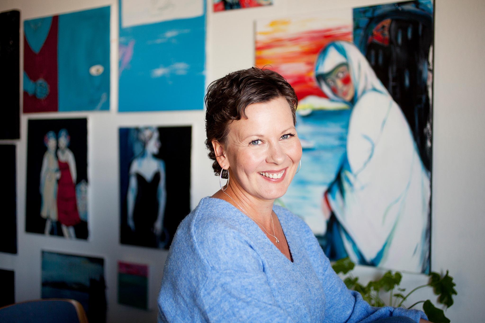 Kirjailija Krista Launonen hymyilee. Taustalla maalauksia.