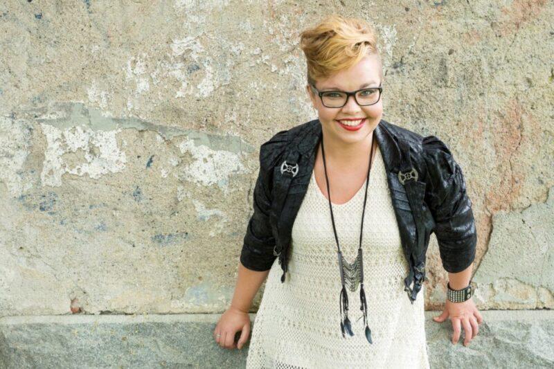 Valkoiseen mekkoon ja mustaan nahkatakkiin pukeutunut kirjailija Salla Simukka nojaa vaaleaan kivitalon seinään.