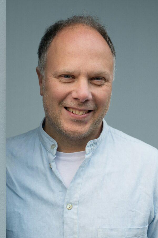 Författaren Magnus Londén. Londén har ljusblå skjorta och han ler. Kirjailija Magnus Londén. Hänellä on päällään vaaleansininen paita ja hän hymyilee.
